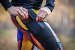 Kieszonka na udzie w kolorowych długich leginsach do biegania dla aktywnych kobiet